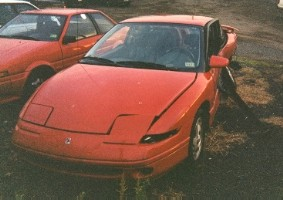 Banged-up red 1995 Saturn SC2